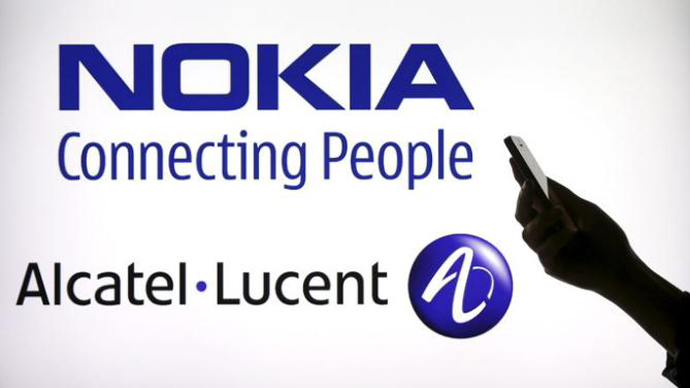 A woman holds a smartphone in front of a screen displaying both Nokia and Alcatel Lucent logos in this photo illustration in Paris, April 14, 2015. REUTERS/Benoit Tessier